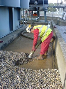 dry vac unit removing contaminated pebbles